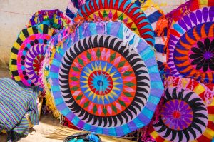 Colorful handmade kites for sale on the street. Locals display huge circular kites called barriletes & fly smaller ones each year in the cemetery on All Saints' Day to honor spirits of the dead.