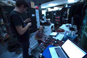 Samantha Palumbo seated at a sound board in an equipment room talking with another technician