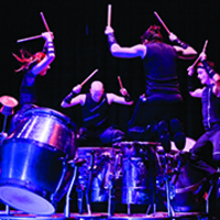 Musicians standing in a circle beating drums