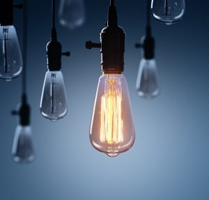 Light bulbs hanging from the ceiling, one is lit.
