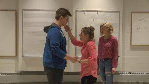 Two students hold hands while one other stands behind during a practice of A Midsummer Night's Dream