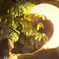Woman holding a glowing crescent moon with a tree behind on stage.