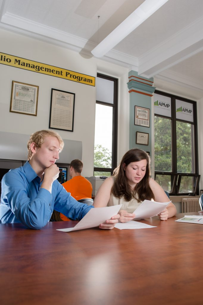 Two students sitting at a conference table studying.